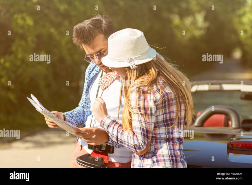 happy friends with map driving in cabriolet car at country and Stock     happy friends with map driving in cabriolet car at country and pointing  finger to something ahead