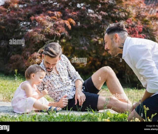 Gay Couple Playing With Their Child In The Garden Stock Image