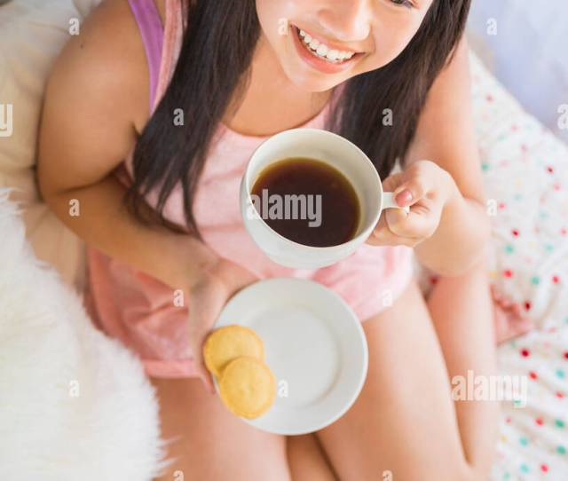 Lifestyle Angled Portrait Of A Beautiful Young Happy Asian Woman Holding A Cup Of Hot Tea