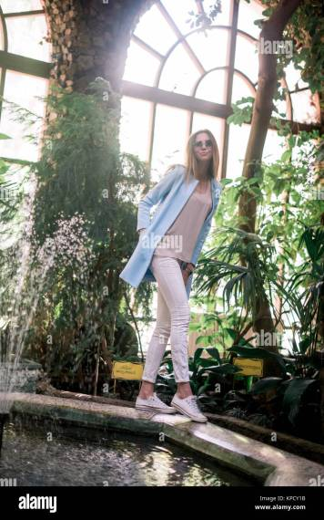 The young elegant positive girl poses in a botanical garden wearing     The young elegant positive girl poses in a botanical garden wearing blue  jacket