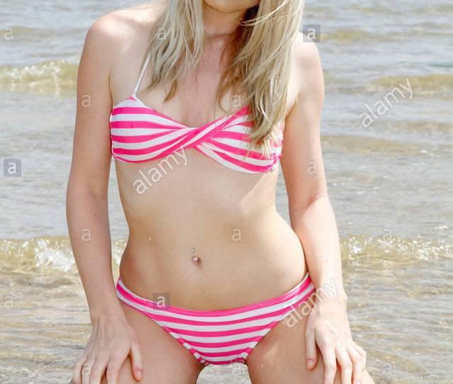Blonde Girl In Pink And White Striped Bikini On Beach
