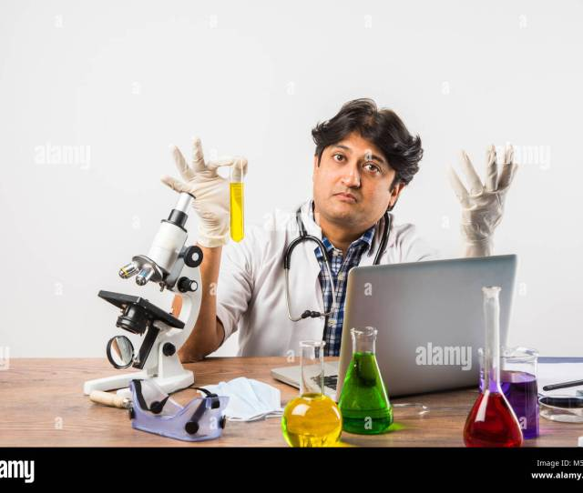 Asian Indian Male Scientist Or Doctor Or Science Student Experimenting With Microscope And Chemicals