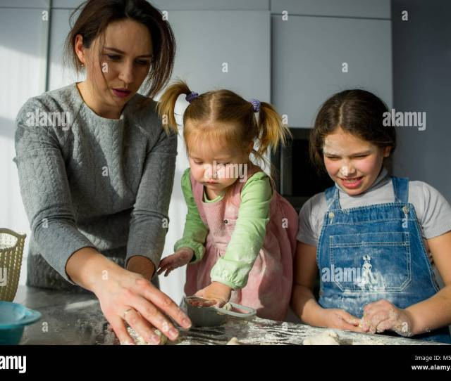 Mom Teaches Two Little Daughters To Cook From Dough Children With Pleasure Are Engaged In Kitchen Work