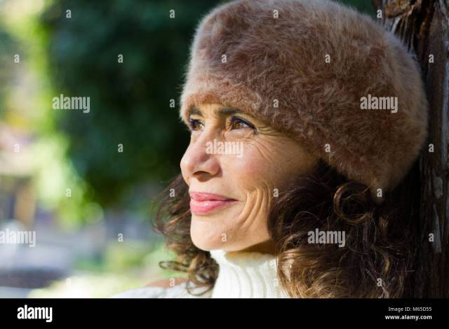Bright Close Up Portrait Of Dazzling Mature Woman Wearing Hairy Fur Beret Hat And Leaning On Tree In Park Middle Aged Lovely Smiling Lady Portrait