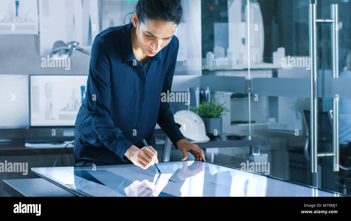 Talented Young Female Architectural Designer Draws Building Concept On A Graphics Tablet Display Clean Minimalistic Office Concrete Walls Stock Photo Alamy