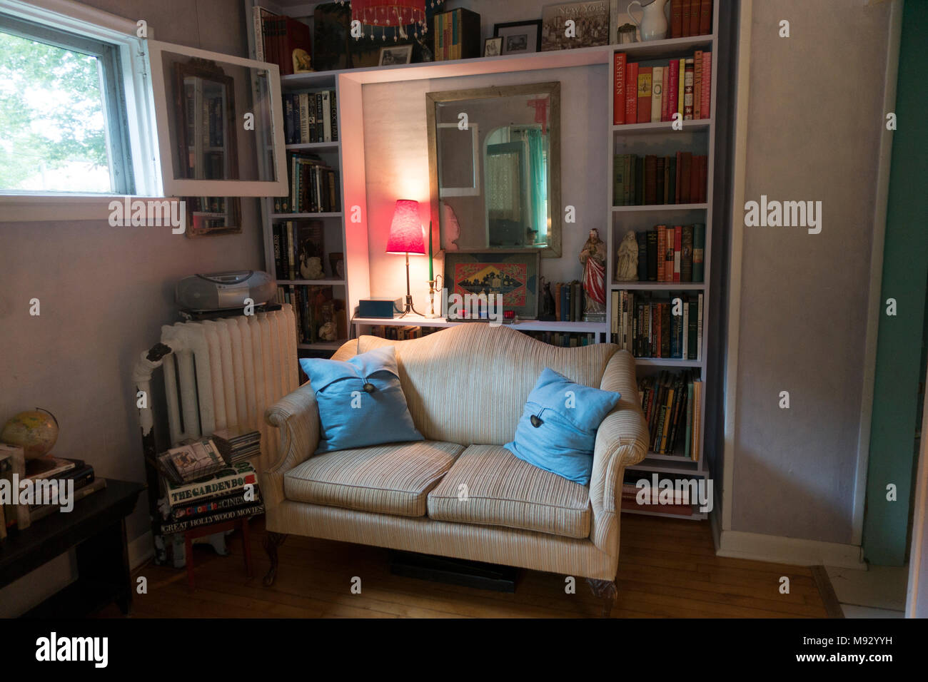 cozy corner of a tiny house with a love seat sofa surrounded by books and objets
