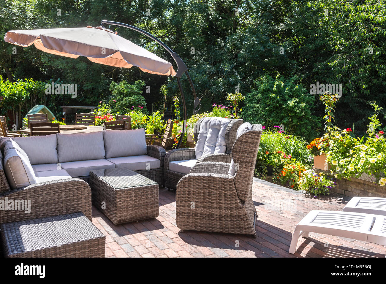 https www alamy com modern rattan patio furniture with dining table and chairs with parasol in the background all surrounded by greenery and flowers image177750514 html