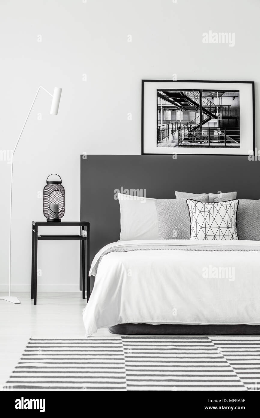 Black Table Next To A White Bed With Poster In Minimal