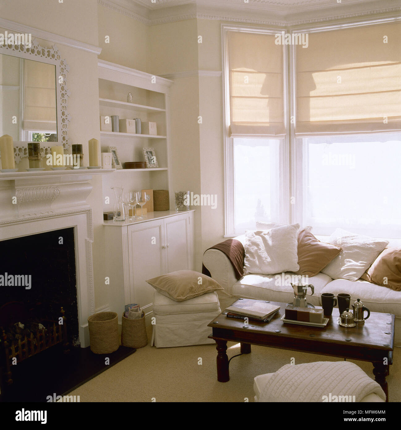 https www alamy com traditional sitting room with a fireplace built in cabinetry overstuffed sofa and footstool wooden coffee table and roman blinds over a bay window image181877604 html