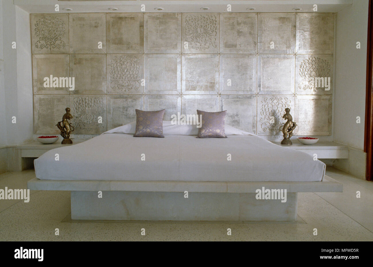 King Size Bed With Marble Platform Against Tiled Wall In