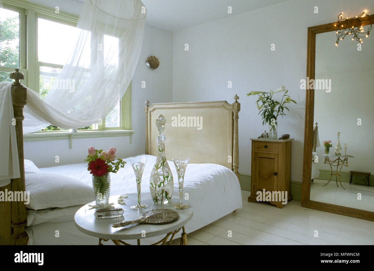 Romantic Bedroom With Sheer Canopy Over A Double Bed Large Mirror Bedside Table And A Sunny Window Stock Photo Alamy