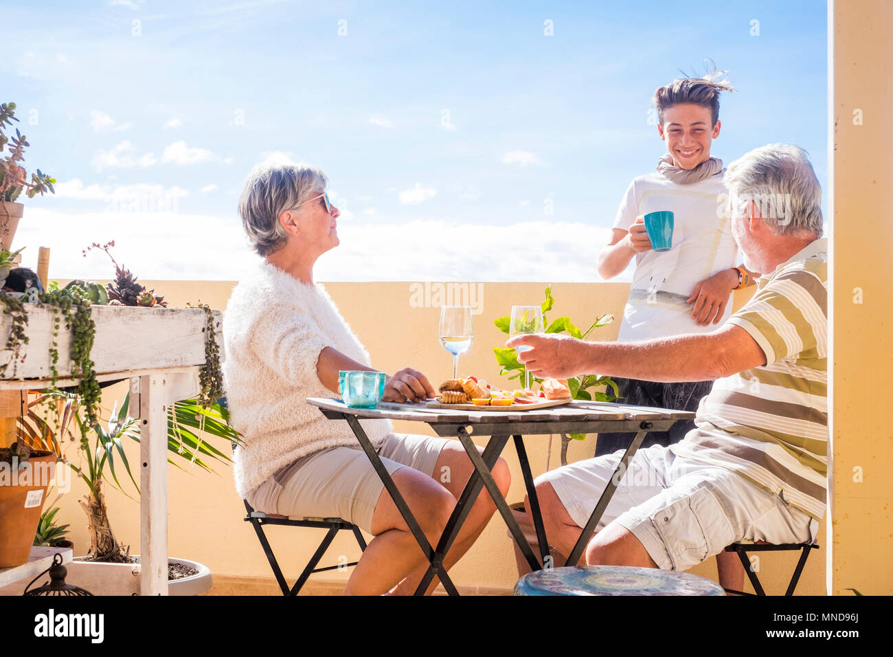 Family With Grandfathers And Teenager Nephew Staying Together Drinking And Smiling Leisure