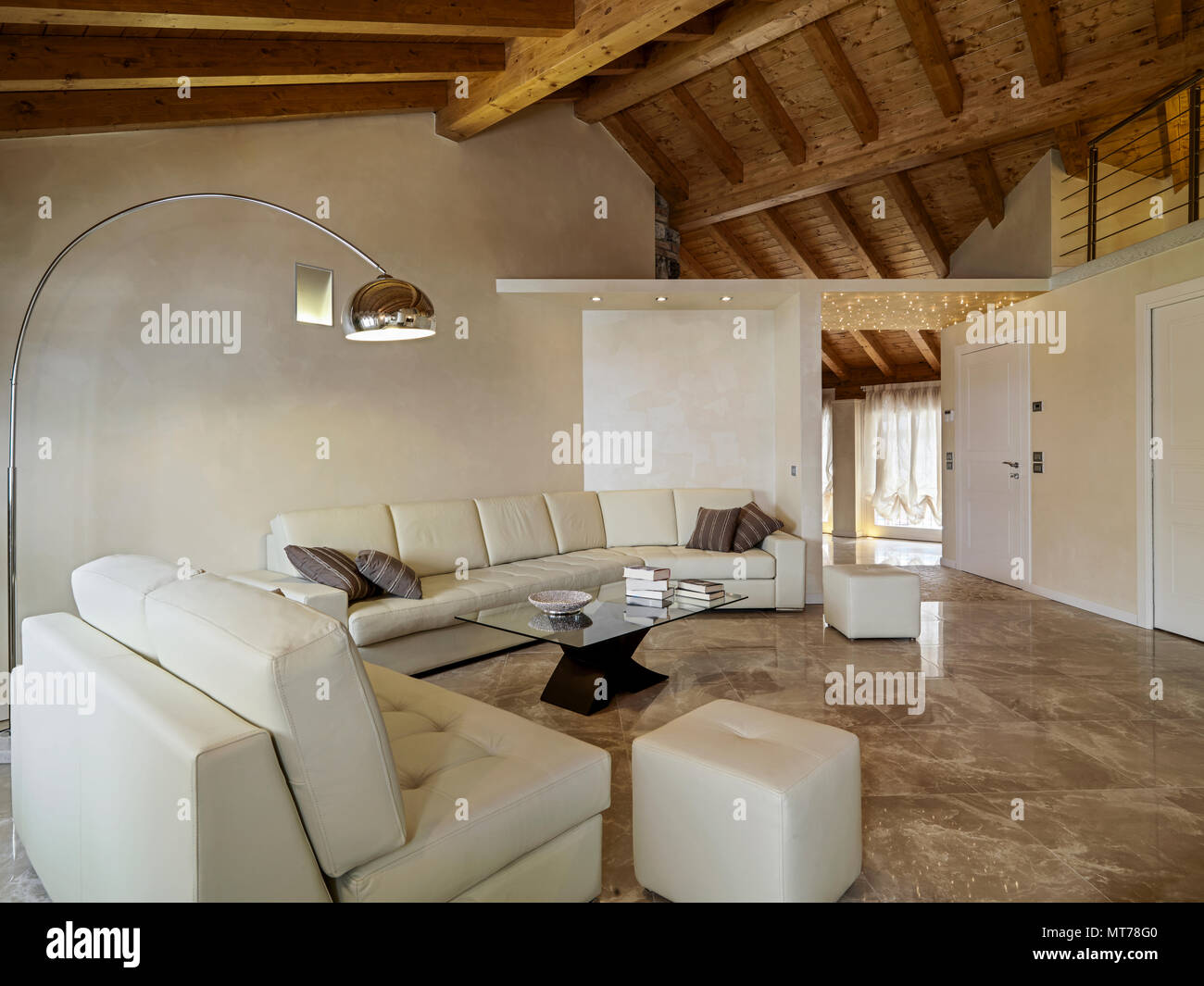 https www alamy com living room interior in foreground the beige leather sofa and the glass coffee table with arch floor lamp the ceiling is made of wooden beams exposed image187015808 html