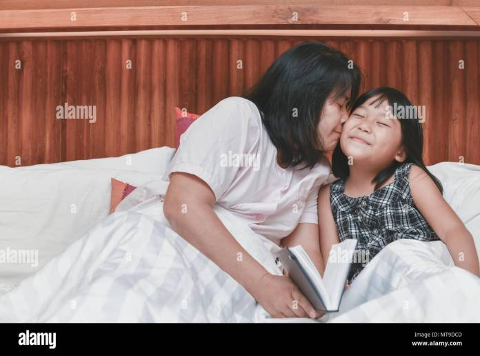 mother is kissing her daughter in cheek after reading book on bed at