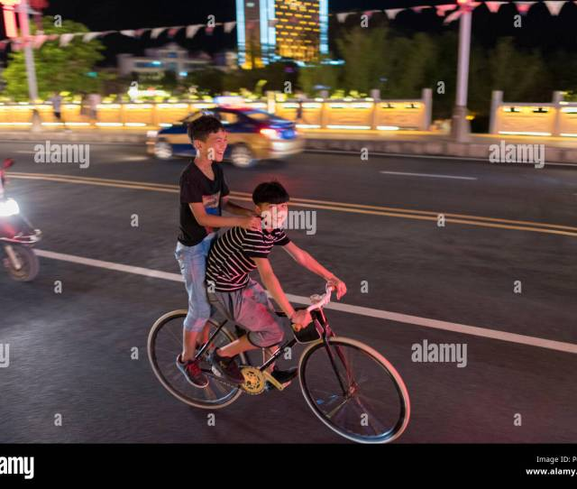 Two Teen Boys Share A Bicycle And Speed Through City Center On Hot Summer Night Libo Guizhou Province China