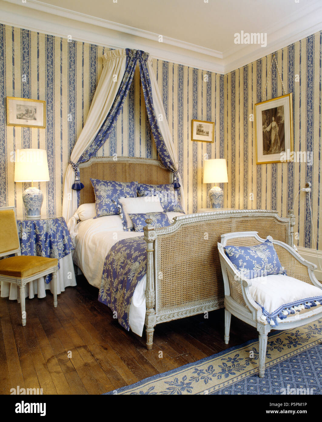 Antique Bergere Bed With Blue Drapes In French Country Bedroom With Blue White Striped Wallpaper And Lighted Lamps Stock Photo Alamy