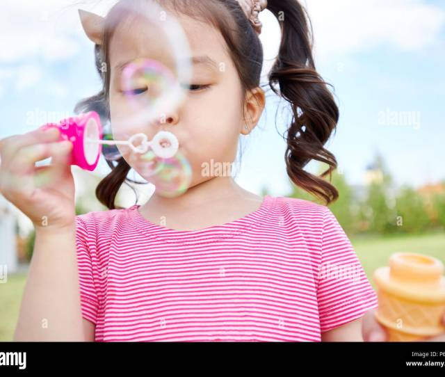 Cute Asian Girl Blowing Bubbles Outdoors