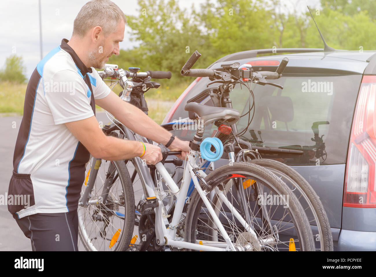 https www alamy com man wearing sportswear loading bicycles on the bike rack mounted to a car towbar image214404806 html