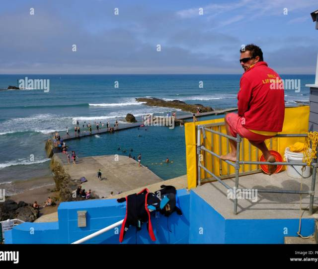 Bude Cornwall Uk Rnli Lifeguard Watches Over Swimmers Enjoying The Hot Weather And Water In One Of Budes Semi Natural Sea Bathing Pools