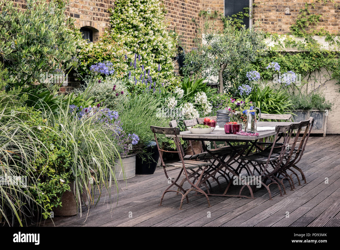https www alamy com old french bistro chairs around long wooden table on garden roof terrace with decking agapanthus and jasmine flourishes in the background image214715443 html