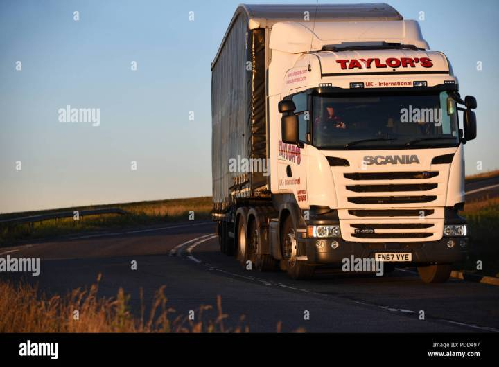 Scania Truck Pulling A Curtainsider Trailer Takes Corner On The Woodhead Pass Yorkshire At Dusk