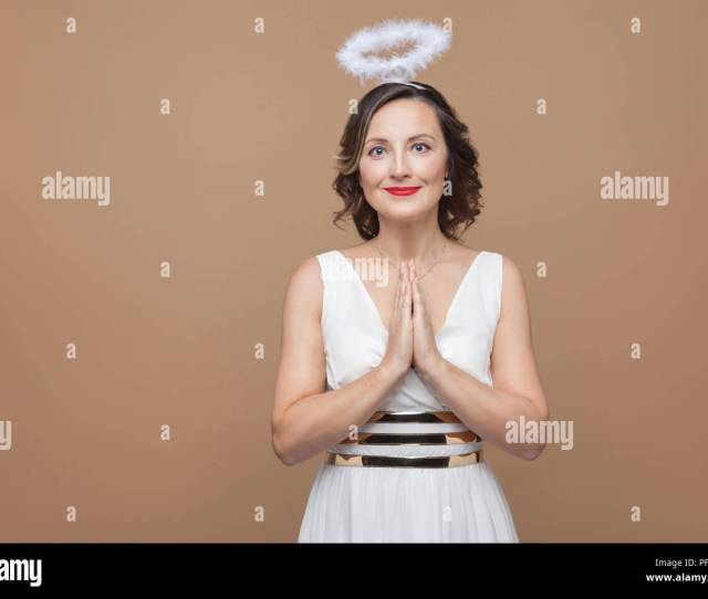 Elegant Angel Brunette Woman In White Dress And Nimbus In Top Of Her Head Pray And Looking At Camera With Smile Emotion And Feeling Concept Studio S