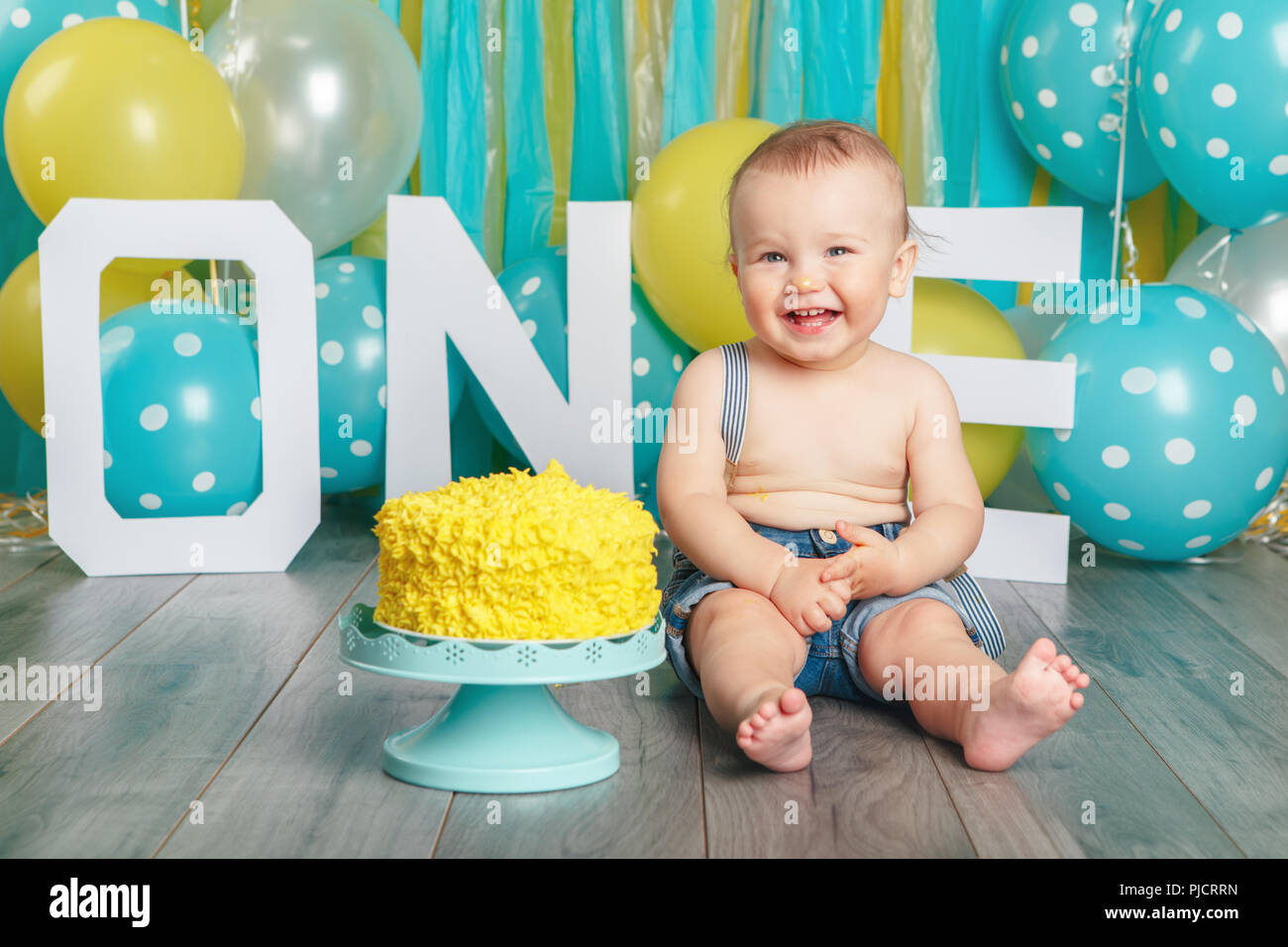 Portrait Of Cute Adorable Caucasian Baby Boy In Jeans Pants Celebrating His First Birthday Cake Smash Concept Child Kid Sitting On Floor In Studio E Stock Photo Alamy