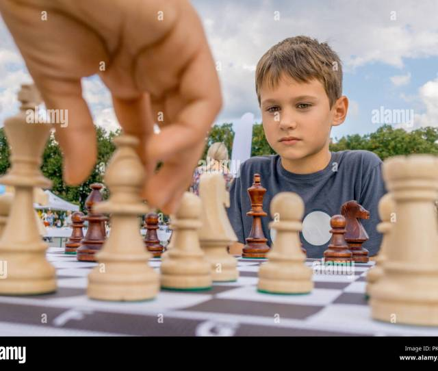 Children Playing Chess At Chessboard Outdoors Boy Thinking Hard On Chess Combinations