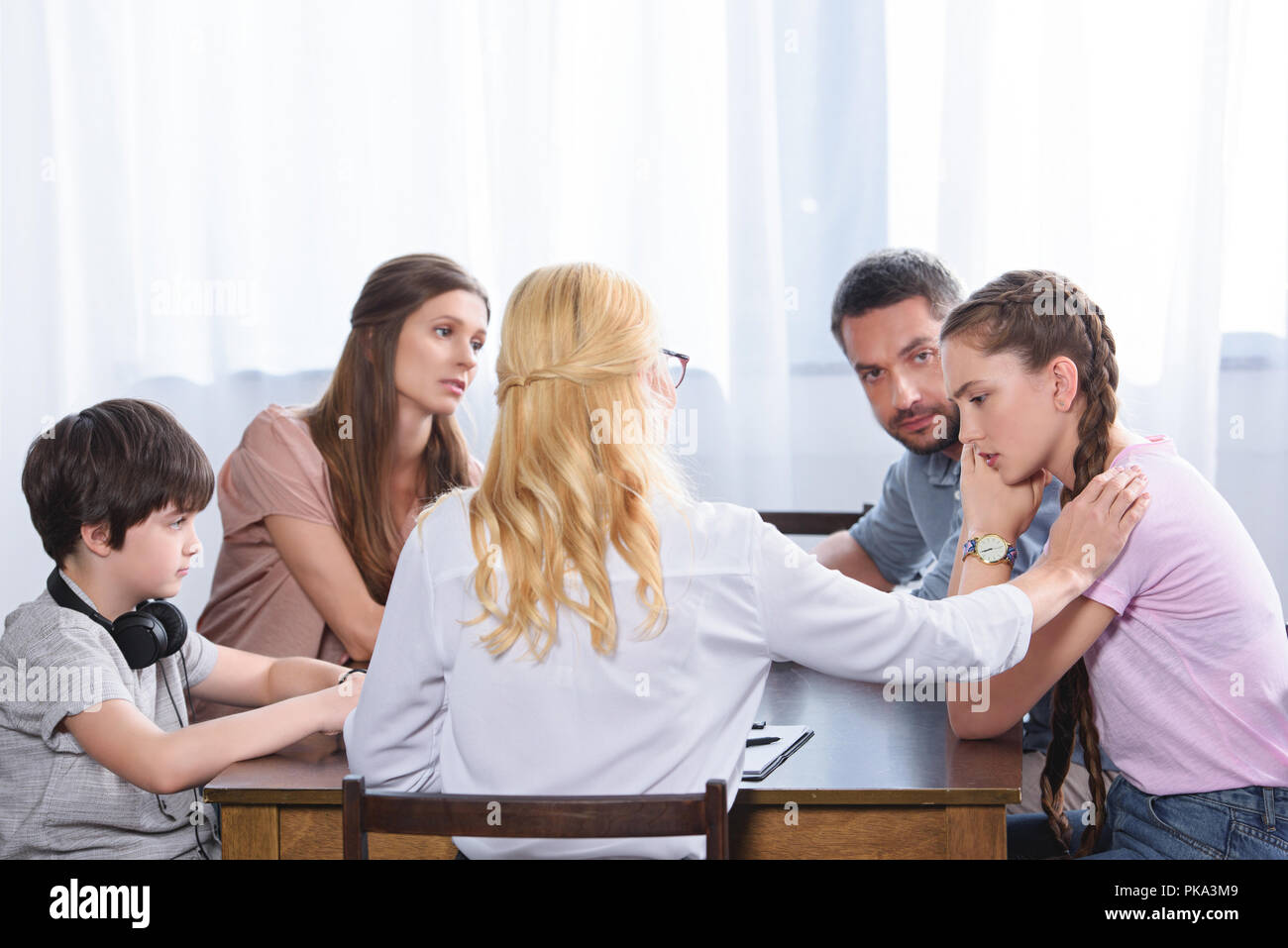 Rear View Of Female Counselor Cheering Up Upset Teenage
