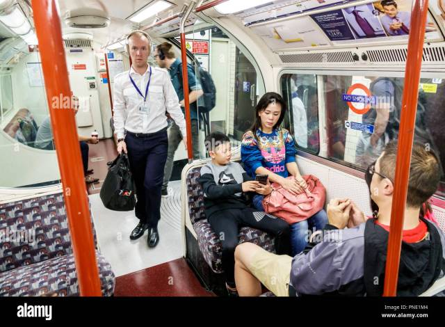 North Underground Station Subway Tube Public Transportation Mass Transit Train Carriage Inside Riders Passengers Man Asian Woman Boy Mother Son Sitting