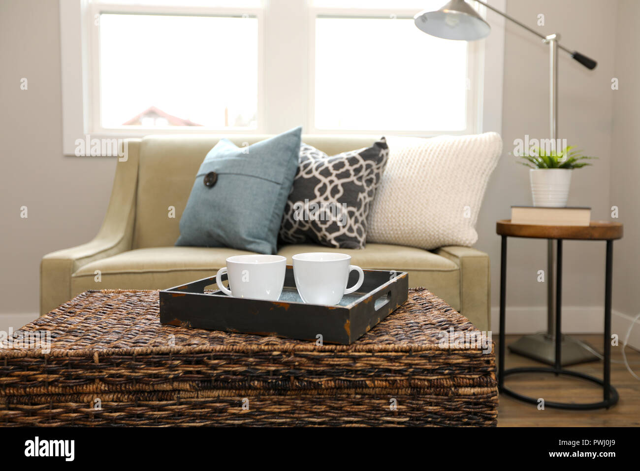 https www alamy com rattan trunk coffee table with a wood tray and white cups next to a beige sofa with colorful pillows image222286465 html