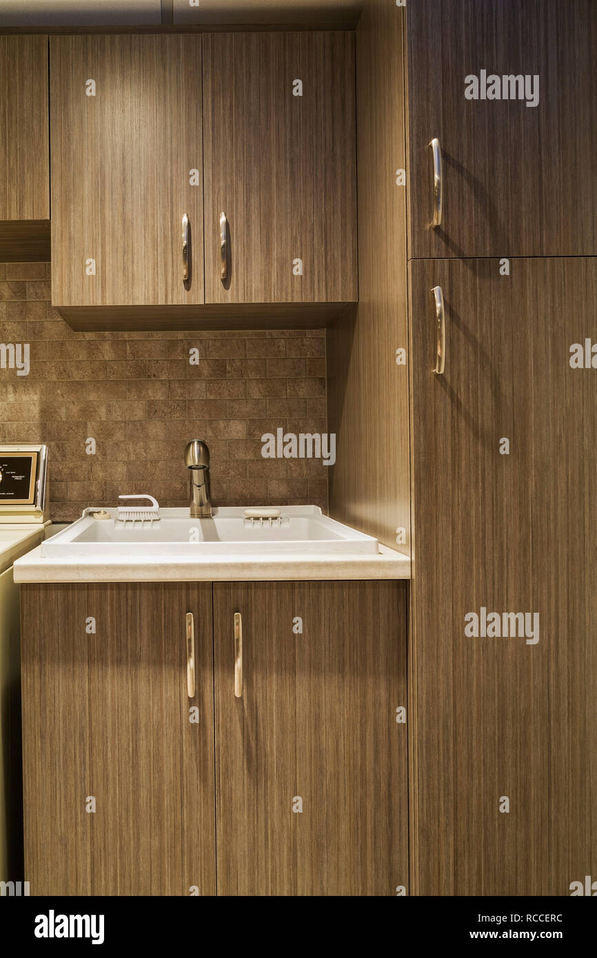 https www alamy com newly installed brown wood veneer cabinets and white utility sink in the laundry roombathroom in basement inside a residential home image231385712 html