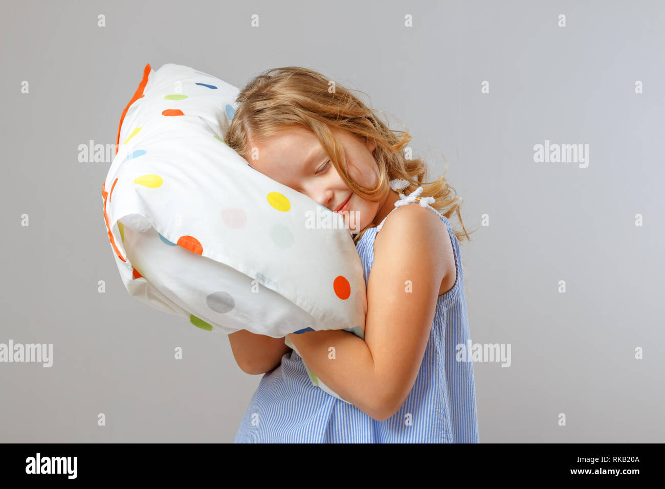 https www alamy com people and healthy sleep concept a little girl kid hugs a soft pillow closes her eyes and poses against a studio background gray background image235656298 html