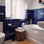 White Plantation Shutters In Bathroom With Blue Tiling Stock