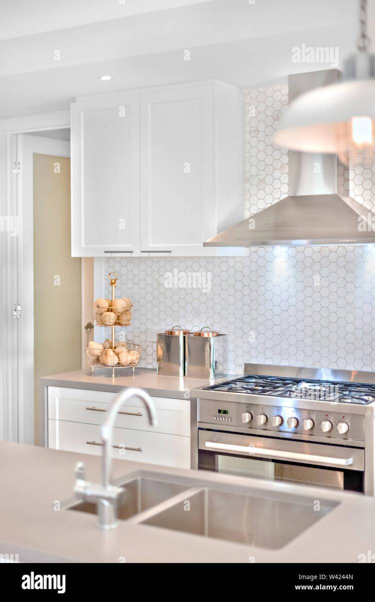 Modern Kitchen Stove With Some Fancy Items On The Counter Top There Is Blurred Tap And Sink Before The Chimney And Pantry Cupboards On The White Wall Stock Photo Alamy