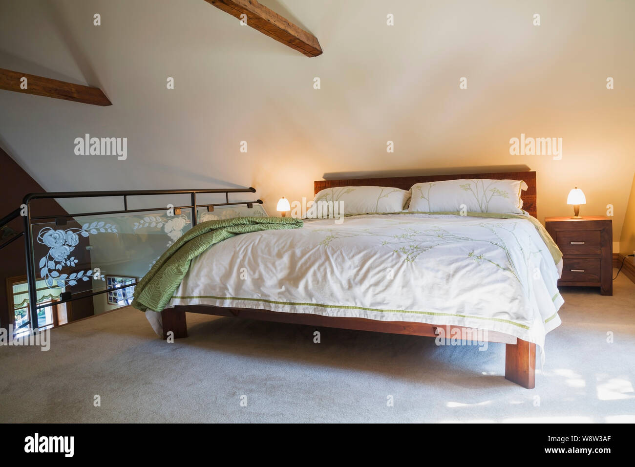 King Size Bed On Teak Wood Frame With End Tables Black Wrought Iron And Tempered Glass Balustrade Old Wooden Structural Beams In Master Bedroom Stock Photo Alamy