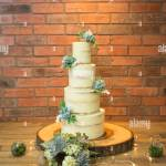 Four Tiered Wedding Cake With Cream Buttercream Icing And Succulents Decorating The Cake Wedding Cake Stock Photo Alamy