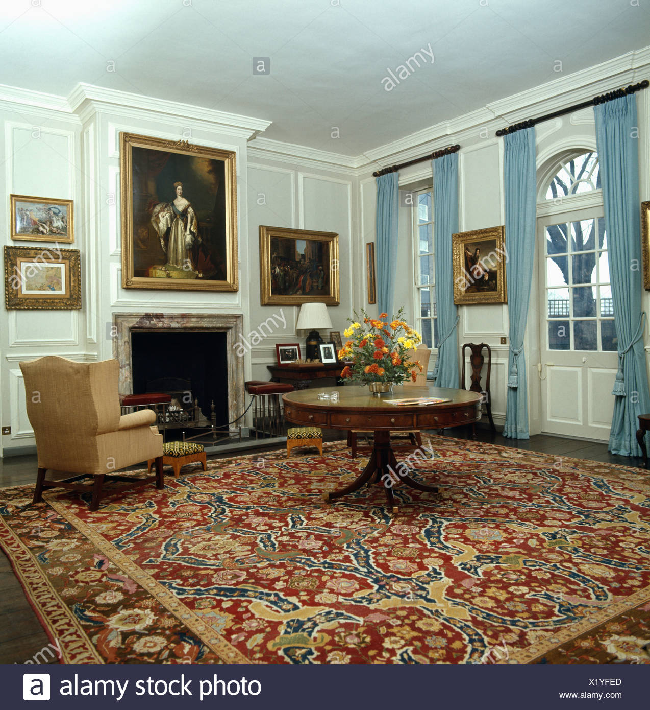 Circular Table On Patterned Red Carpet In Livingroom With