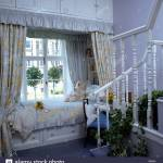 Storage Cupboards Above And Below Bed In Window Of Child S Bedroom With Floral Curtains And Quilt Stock Photo Alamy