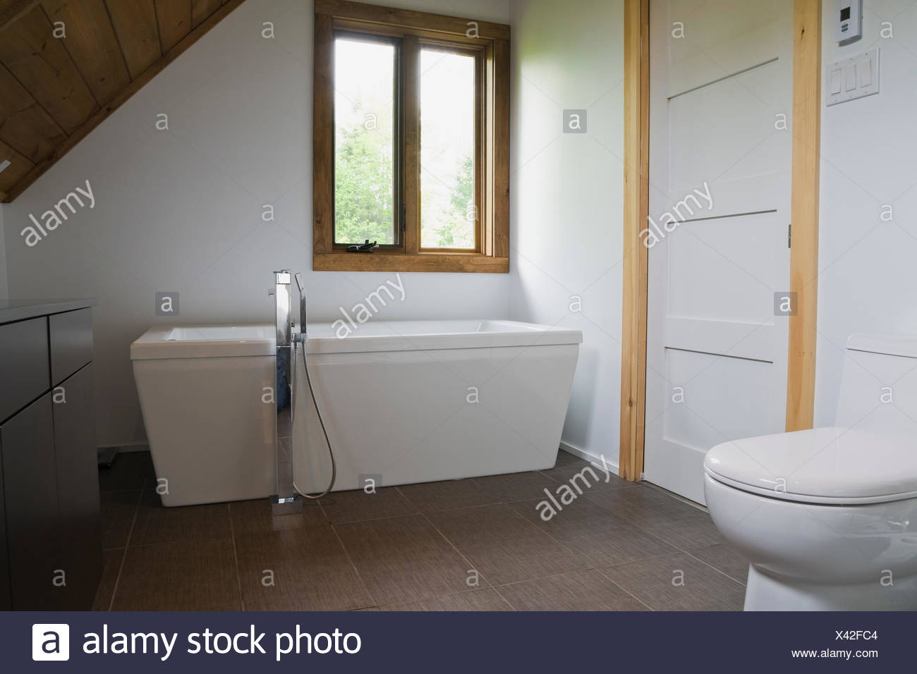 https www alamy com bathroom with grey ceramic tile floor white porcelain toilet and freestanding bathtub in cottage style log home quebec canada image277880516 html