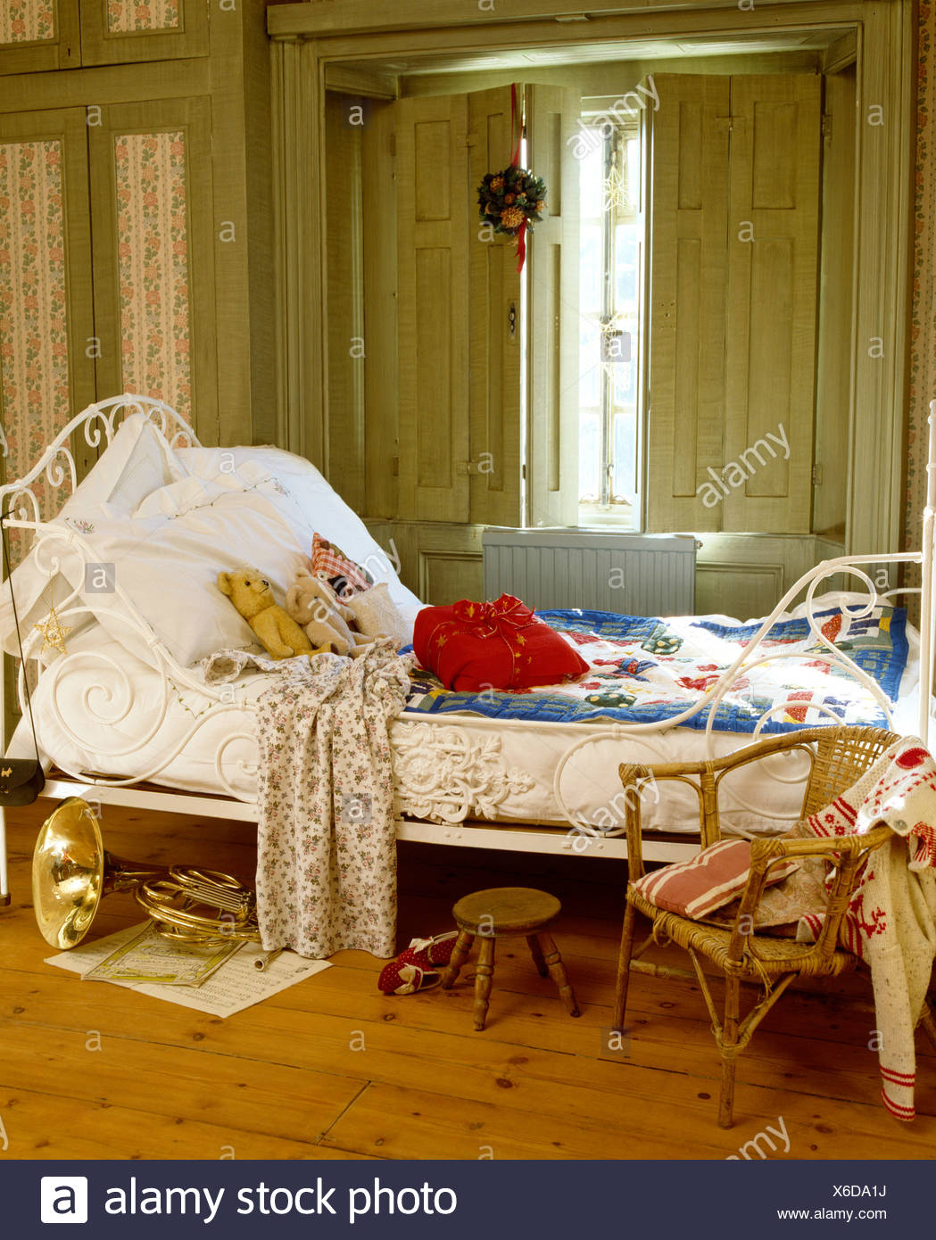 White Pillows And Blue Quilt On Antique Wrought Iron Bed In Front Of Window With Painted Shutters In Child S Bedroom Stock Photo Alamy