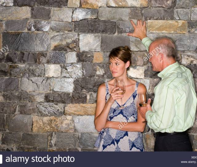Mature Man Flirting With Younger Woman Beside Stone Wall Holding Glasses Of White Wine Woman Looking