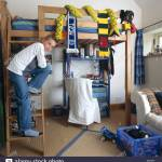 Portrait Of Young Teenage Boy Standing On Bunk Bed Ladder In Bedroom Stock Photo Alamy
