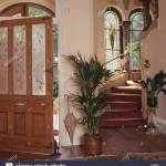 Green Houseplants On Either Side Of Staircase In Cream Hall With Open Front Door With Engraved Glass Panels Stock Photo Alamy
