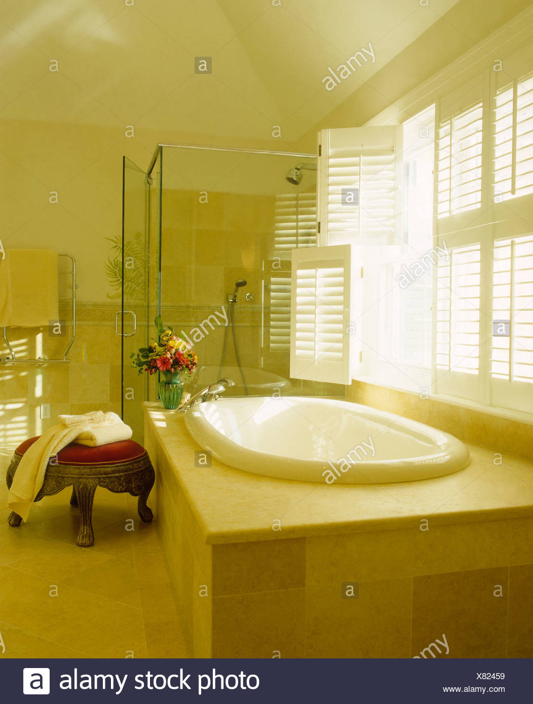 Oval Bath With Pale Wood Surround Below Window With