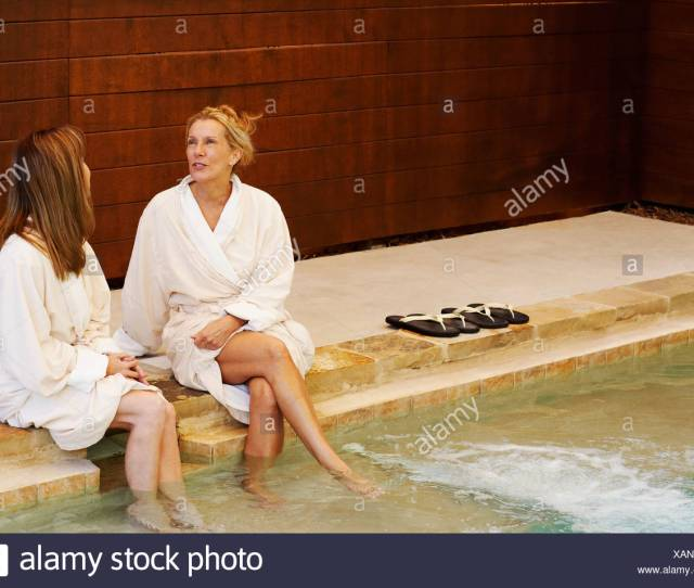 Midi Adult Woman With A Mature Woman Sitting On The Ledge Of A Hot Tub