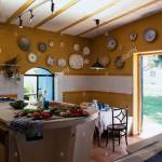 Vegetables On Concrete Island Unit In Yellow Spanish Kitchen With Collection Of Pottery Plates On Wall Above White Tiled Panel Stock Photo Alamy