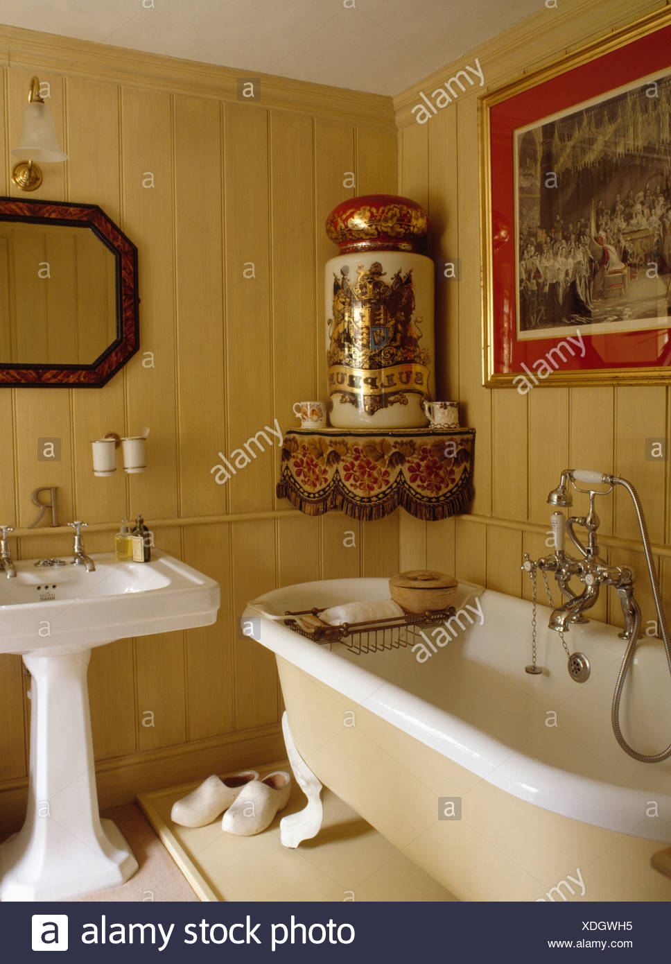 Large Antique Pot On Corner Shelf Above Clawfoot Bath In Neutral Panelled Bathroom With White Pedestal Basin Stock Photo Alamy