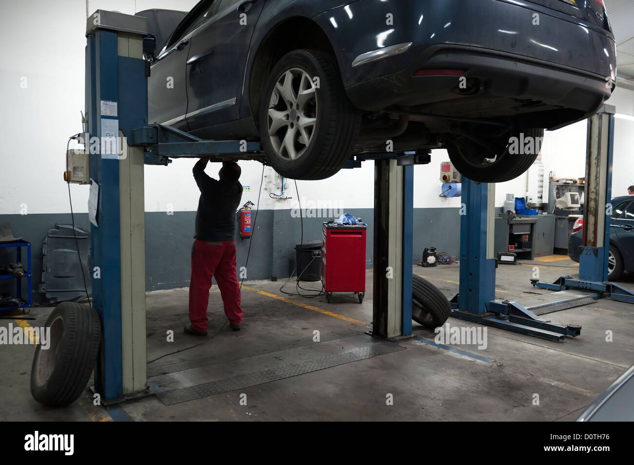 Kfz Mechaniker Uberpruft Ein Auto Auf Einer Hebebuhne Angehoben Stockfotografie Alamy