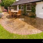 Design Garten Mit Gebogenen Gepflasterte Terrasse Rasen Gitter Holzernen Tisch Stuhle Von Garage Des Hauses West Yorkshire England Uk Stockfotografie Alamy